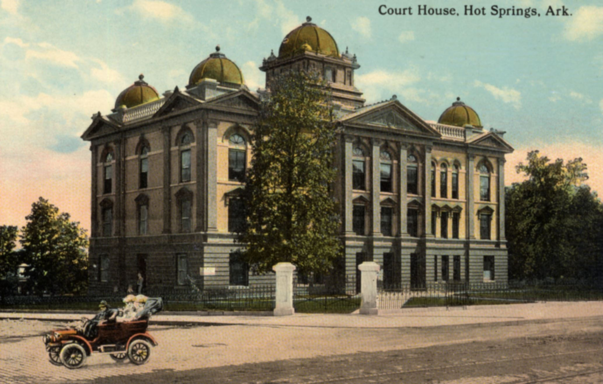 Tan colored Garland County Courthouse with tree and old car driving by on street- Years 1905-1913