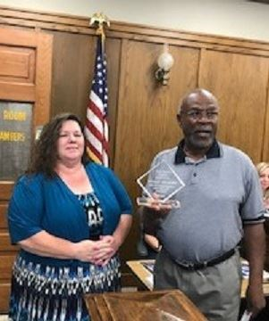 Woman in colorful blue dress receives glass award from man in gray shirt