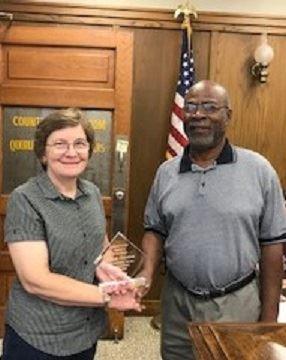 Woman in dark gray shirt and man in light gray shirt shake hands as woman accepts glass award