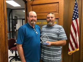 Man in blue shirt presents a glass award to man in striped shirt